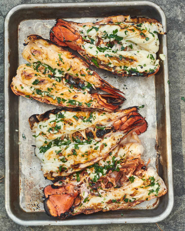 four grilled lobster tails on a  baking pan