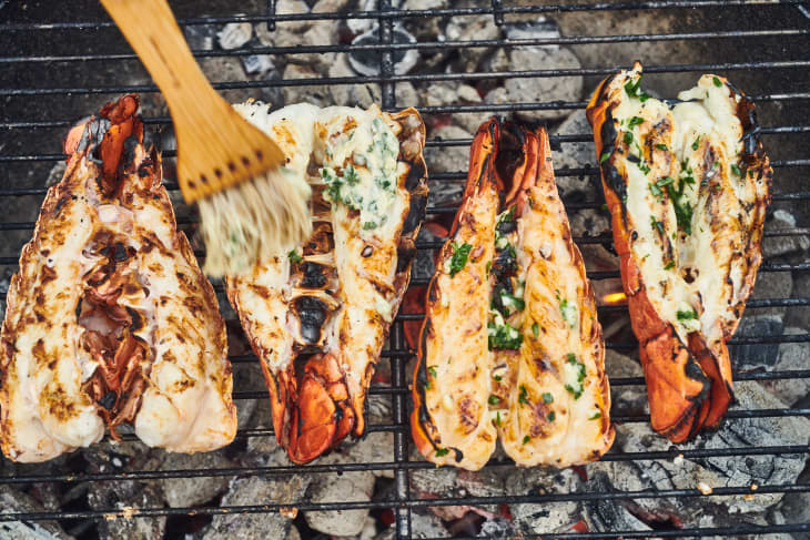 four grilled lobster tails on a grill being brushed with butter