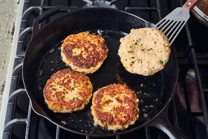 four chicken burgers are cooking in a cast iron pot