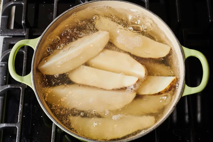 potato wedges boiling in a pot