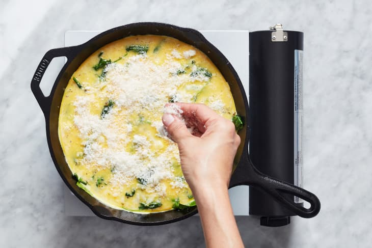 someone putting cheese on fritata in cast iron pan