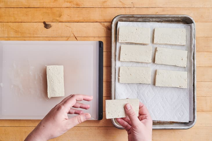 someone is slicing the tofu into squares