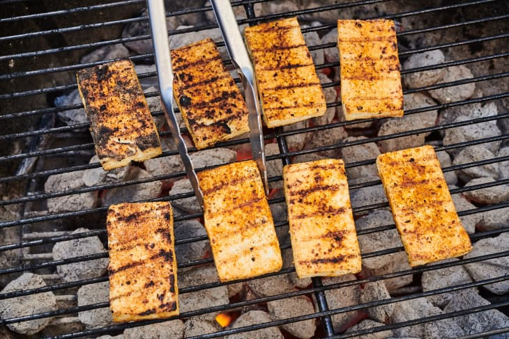 tofu on a grill being flipped