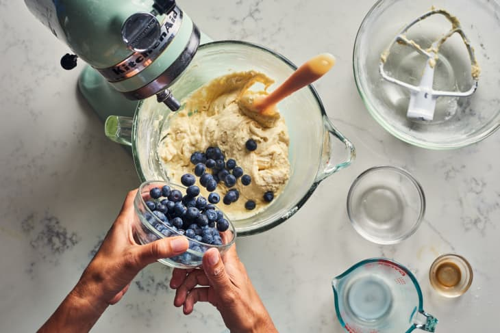 someone pouring blueberries in a stand mixer