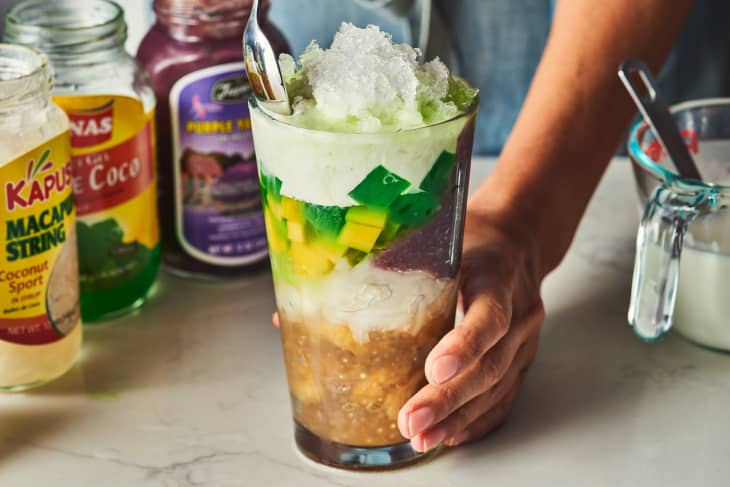 someone stacking ingredients in halo halo, shaved ice on top