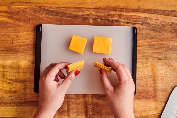Cheese slices on cutting board.