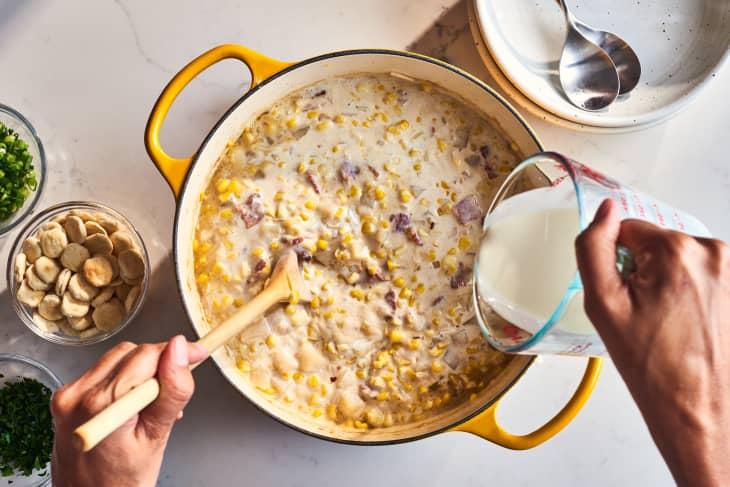 someone adding cream to corn chowder