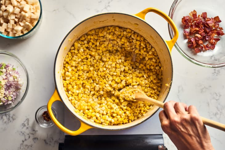 someone mixing corn in pot
