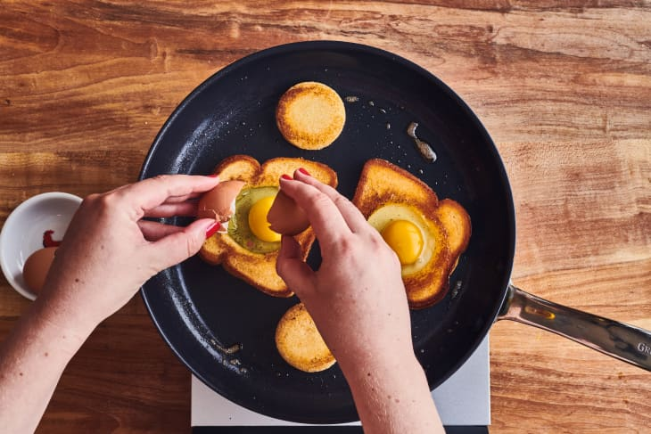 someone adding egg to bread hole in cast iron pan