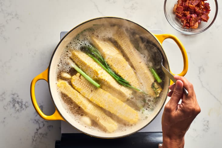 someone boiling corn in a pot